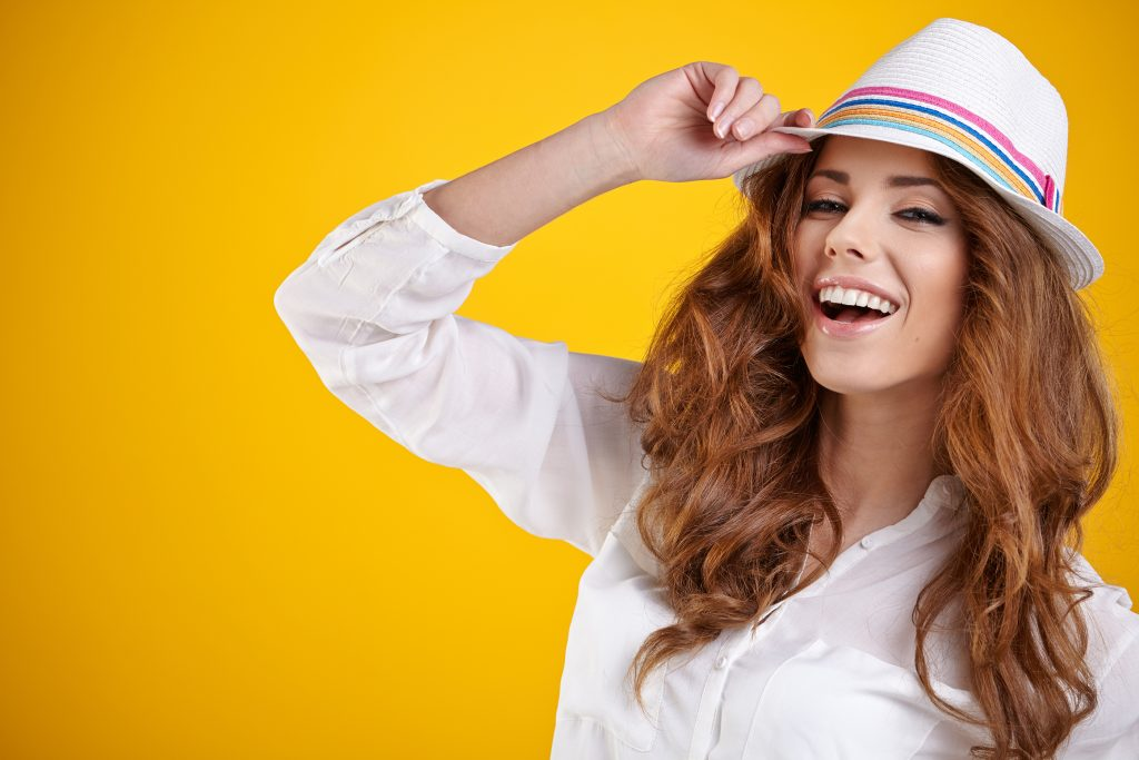 brunette woman with hat in a yellow background