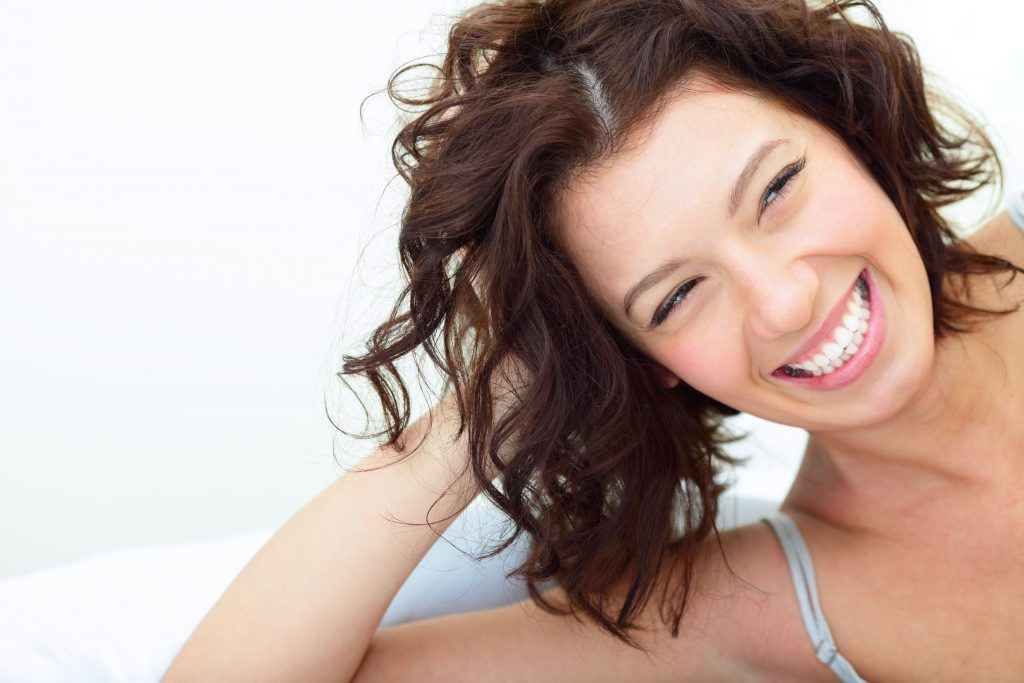 Beautiful woman lying on the sofa and laughing sincerely