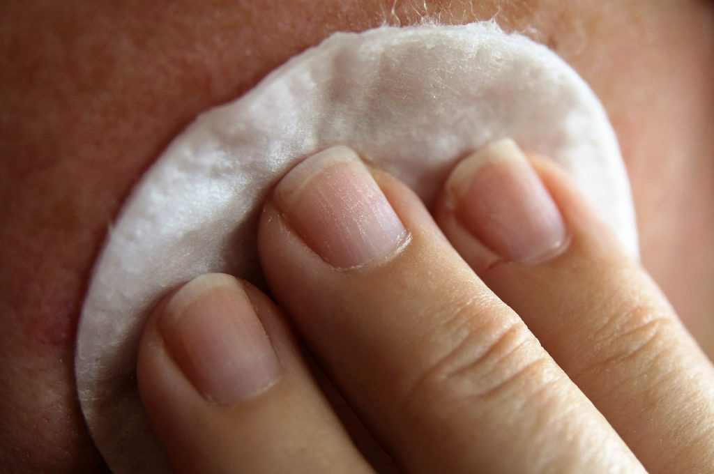 Woman applying skin care with cotton round